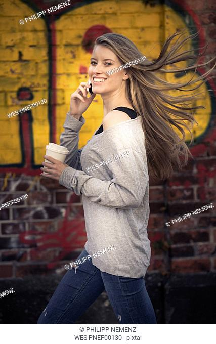 Portrait of laughing woman with coffee to go on the phone