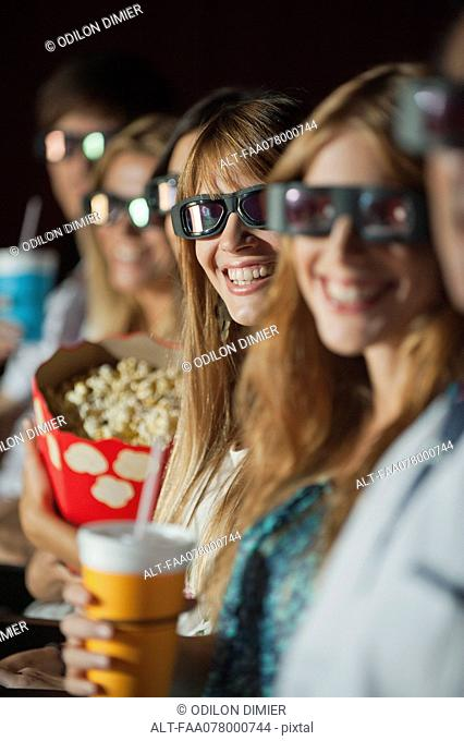 Audience wearing 3-D glasses in movie theater, smiling at camera
