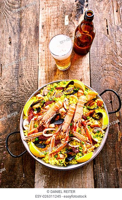 High Angle View of Colorful Spanish Seafood Paella Rice Dish with Fresh Langostino Served in Pan with Handles and Accompanied by Refreshing Beer Beverage on...