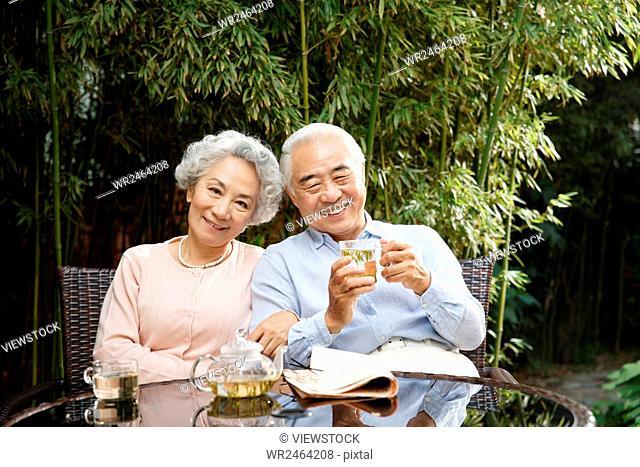 Senior couple sitting in yard