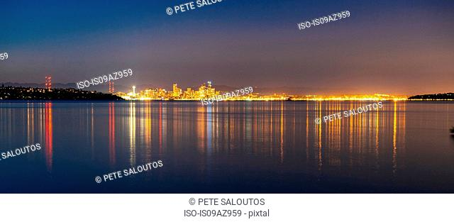 Distant panoramic view of city lights reflected in Puget Sound at night, Seattle, Washington, USA
