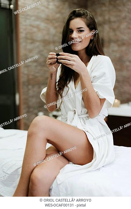 Young woman sitting on lounger in a spa drinking cup of tea