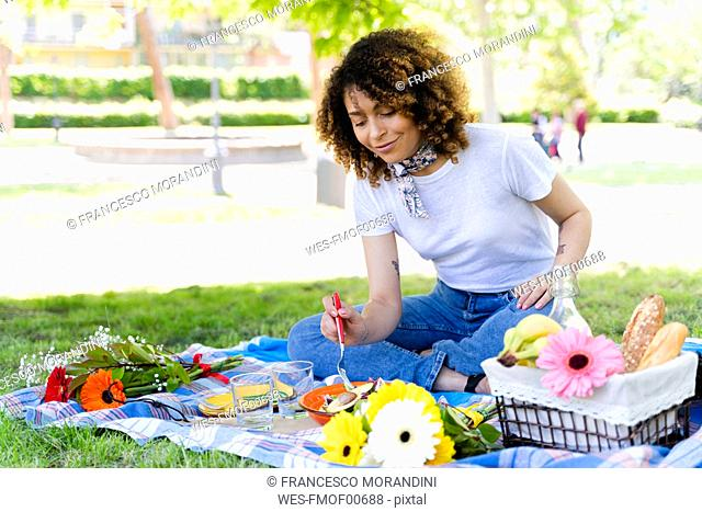Relaxed woman having a picnic in park