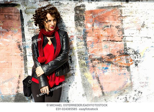 Gorgeous brunette woman posing with graffiti on the street.