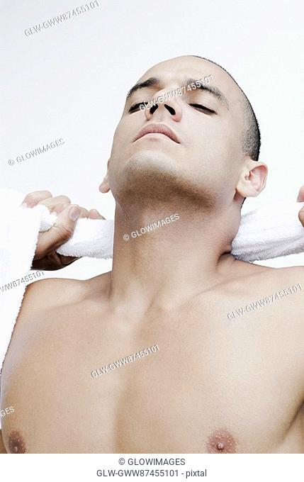 Close-up of a young man wiping his neck with a towel