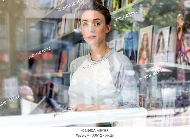 Young woman in a bookshop looking through window