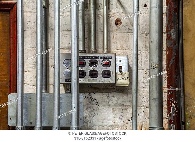 Electrical switches and metal tubing on a brick wall