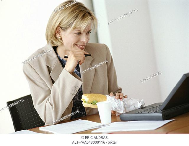 Businesswoman sitting at desk with laptop computer, holding sandwich