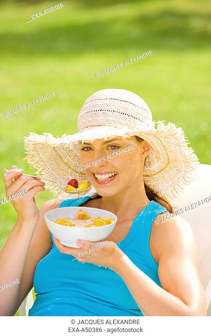 Young woman eating fruits in the garden while sitting in a lounger