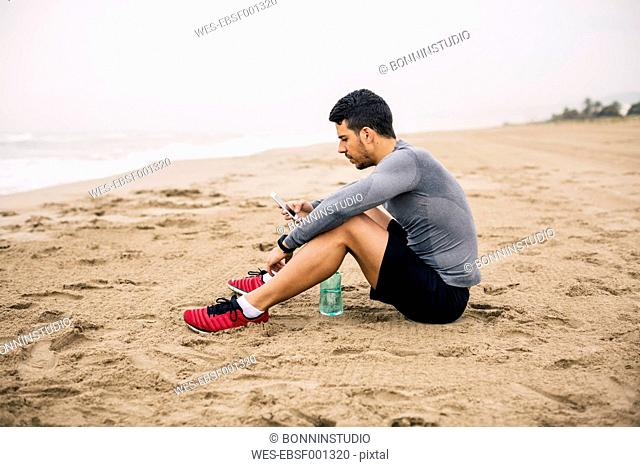 Sportive young man with cell phone and drinking bottle on the beach
