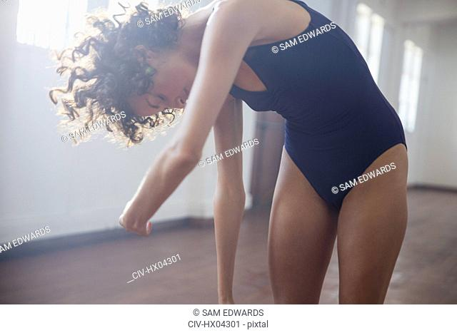 Young female dancer stretching in dance studio