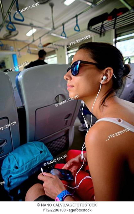 Young woman listens to music in bus, Sri Lanka