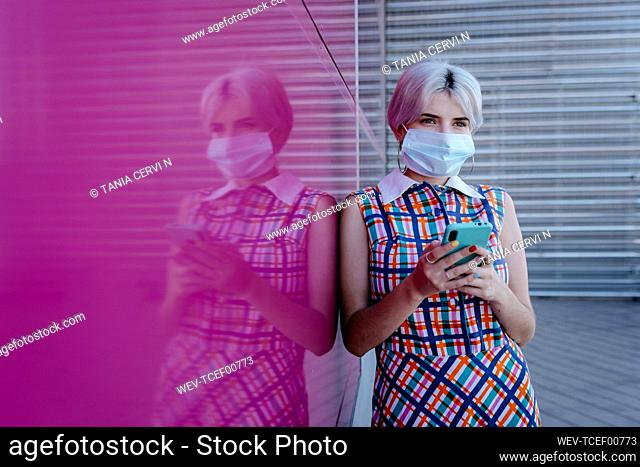 Woman wearing mask using smart phone while standing by pink glass wall
