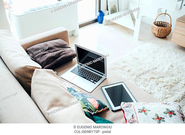 Laptop and digital tablet on sofa