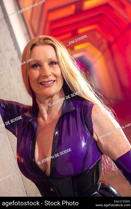 A beautiful 51 year old tall blond woman dressed a latex costume in a lighted underpass