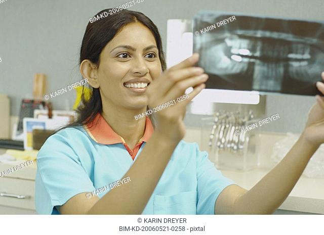 Indian female dental assistant looking at x-rays