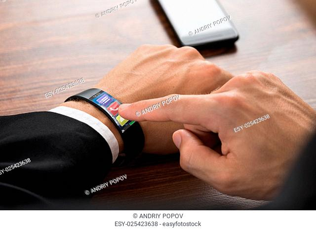Close-up Of Businessman's Hand Wearing Smartwatch Pressing Call Button
