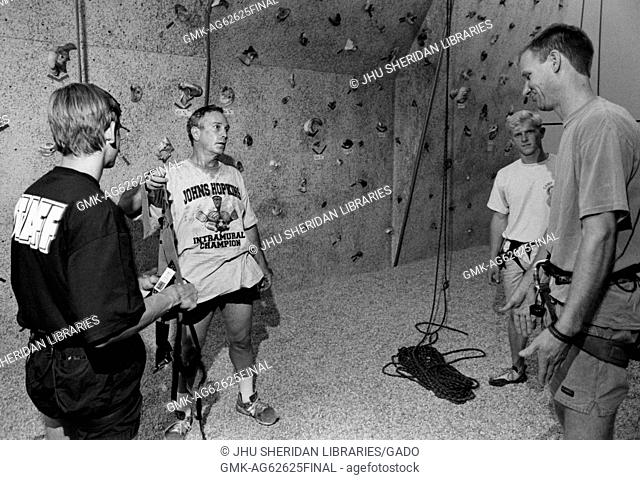Michael Rubens Bloomberg, Candid shot, Bloomberg is standing in front of an indoor climbing wall and holding a climbing harness in his hand while conversing...
