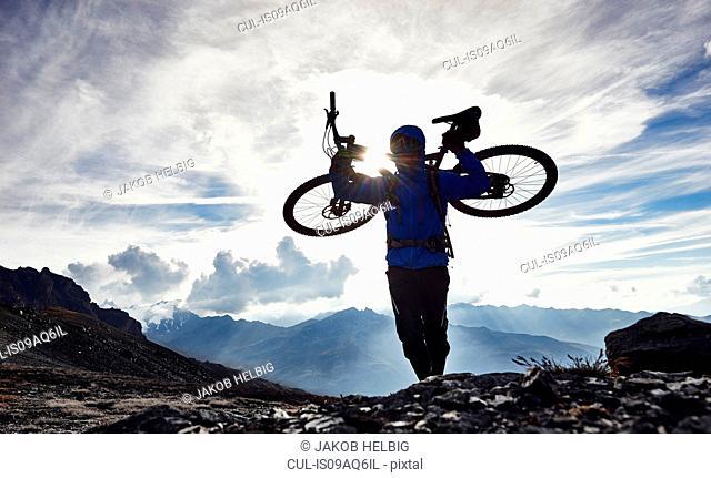 Mountain biker carrying bike, Valais, Switzerland