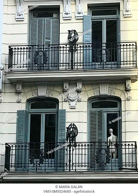 Facade of house and mannequin in window. Serrano street, Madrid, Spain
