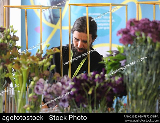 """29 May 2021, Thuringia, Erfurt: Florist Christopher Ernst works on the competition project """"""""Dianthus"""""""" at the State Championship of Florists Hesse-Thuringia at..."""