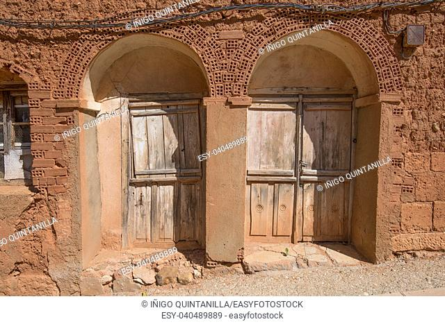 two ancient doors of house built with clay and adobe bricks, in old town of Ayllon village, Segovia, Spain, Europe