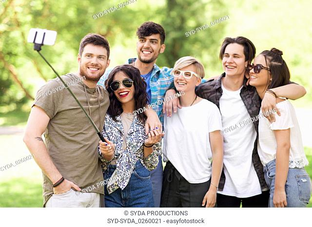 friends taking picture by selfie stick at summer