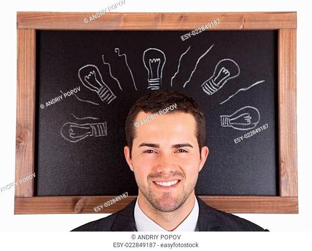 Businessman standing in front on blackboard