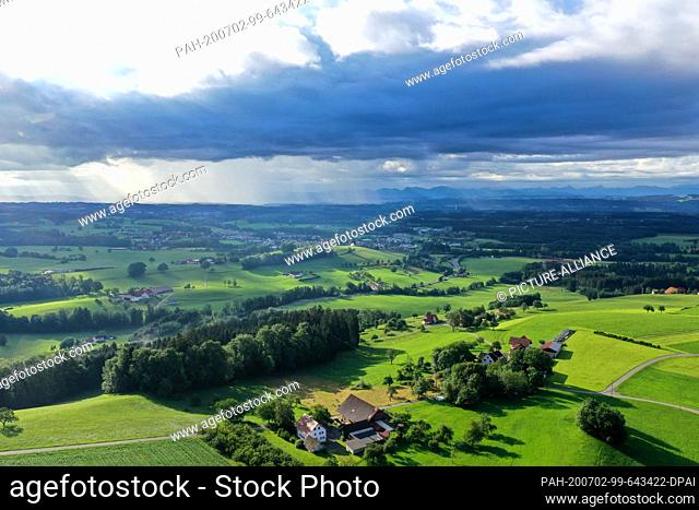 02 July 2020, Baden-Wuerttemberg, Amtzell: Dark rain clouds unload over the foothills of the Alps, while in the foreground a farmhouse is illuminated by the...