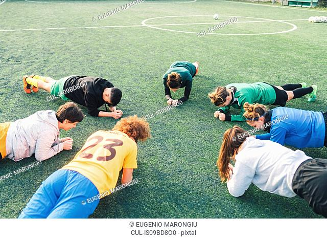 Football players in plank position on pitch