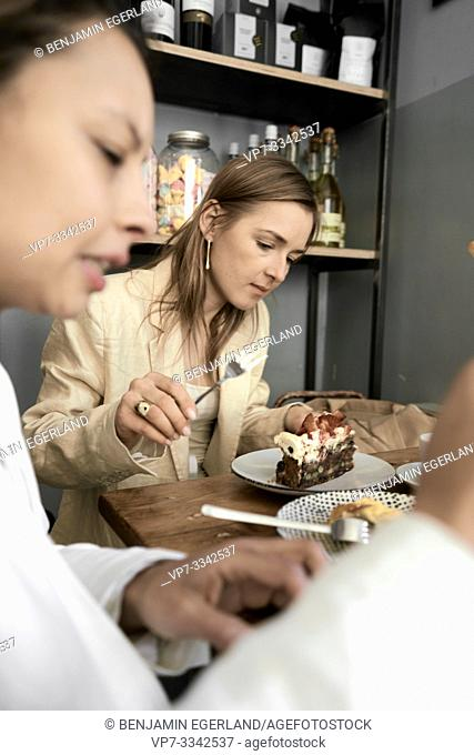 stylish women eating delicious cake in café