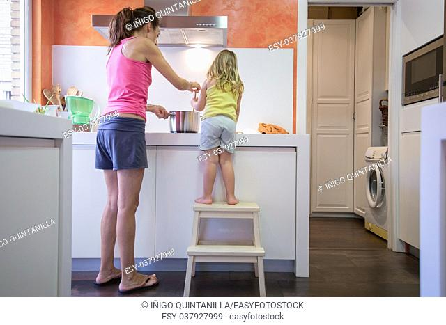 Funny scene. Woman mother and four years old blonde child on stool o ladder cooking together as a team in the kitchen, with a saucepan