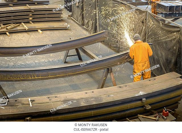 Worker grinding metal construction in marine fabrication factory, high angle view