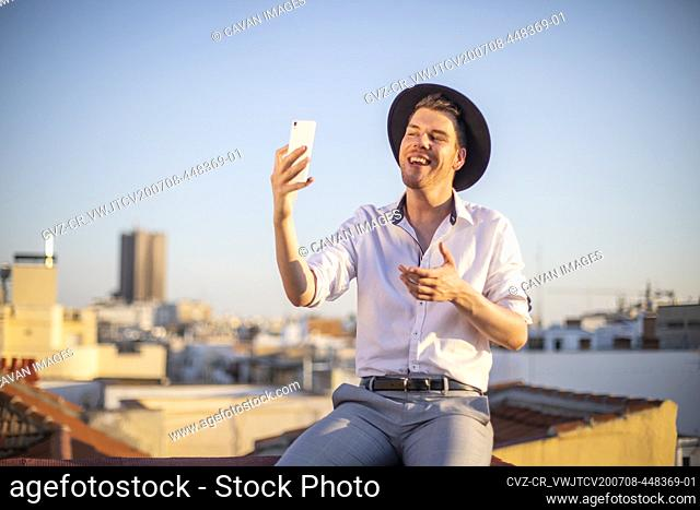handsome young singer performing for his fans on social media from the roof of his house during quarantine