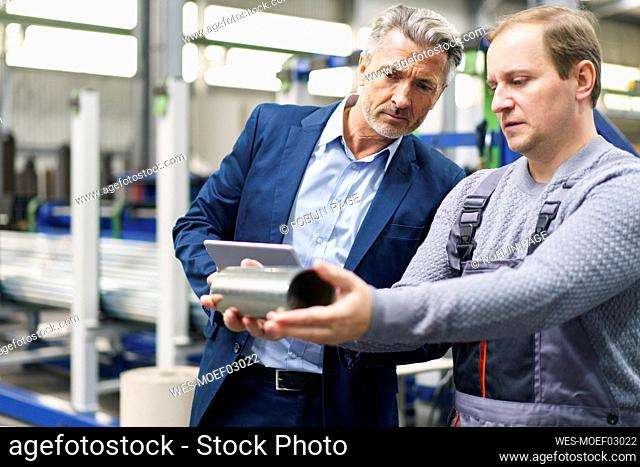 Businessman and worker examining steel pipe in a factory