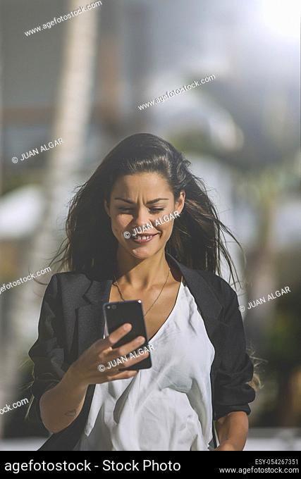 Trendy brunette in black jacket surfing smartphone on territory of tropical resort walking in sunlight