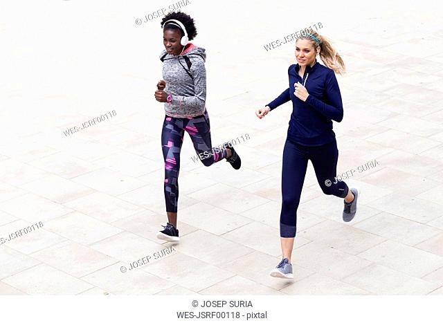 Two sporty young women running together in the city