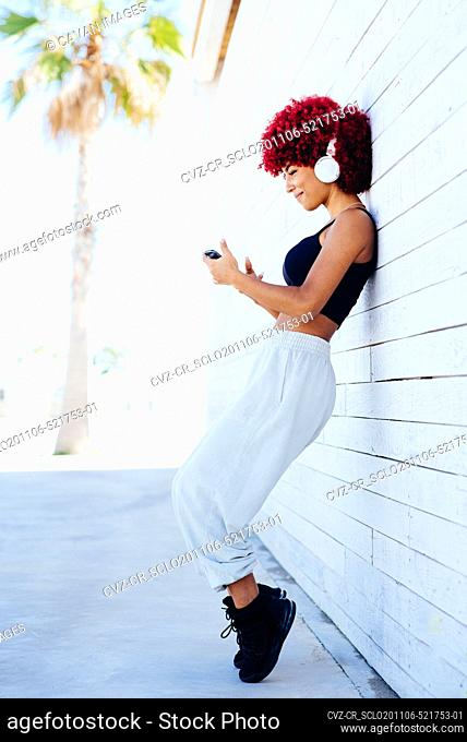 Woman with red afro hair listening music with headphones