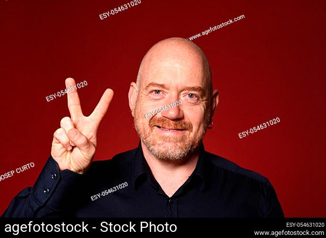 man with sign victory on red background