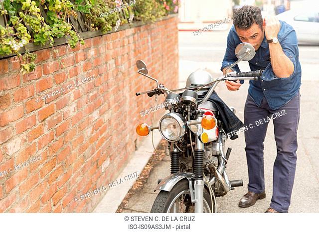 Mid adult man checking hair in motorbike side mirror