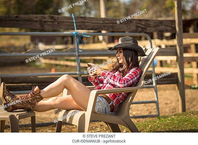 Cowgirl using phone on deckchair on ranch