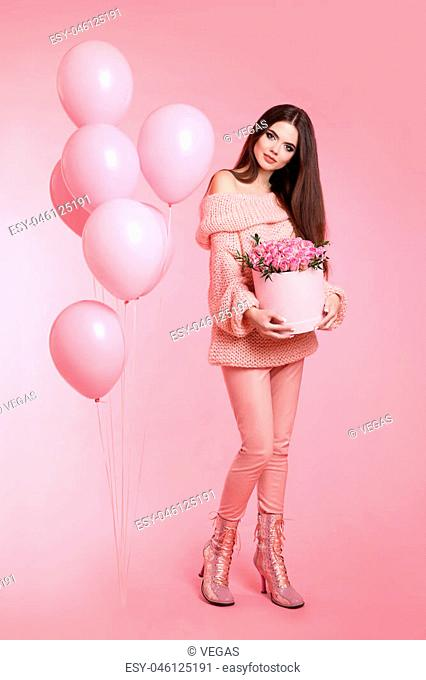 Pretty cute brunette fashionable girl with balloons holding bouquet of rose flowers in hat box isolated on pink studio background. 8 march