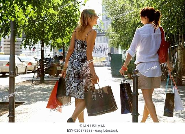 Two woman walking on the street carrying shopping bags