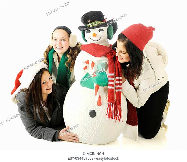 Three young teen girls playing around a Christmas snowman. On a white background
