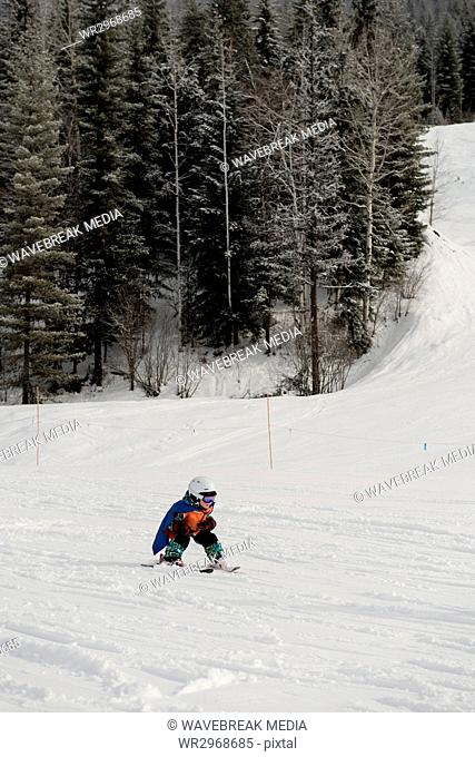 Little boy learning to ski on snowy slope