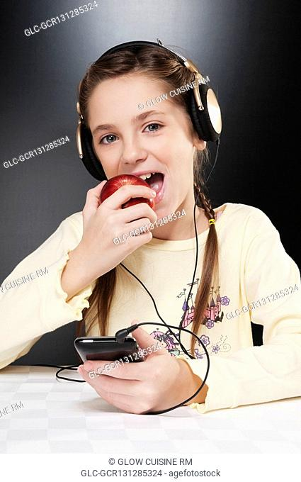 Close-up of a girl listening to music and eating an apple