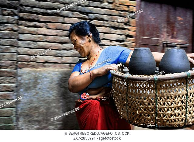 Local woman transport pots to dry in the sun, Pottery Square, Bhaktapur, Nepal