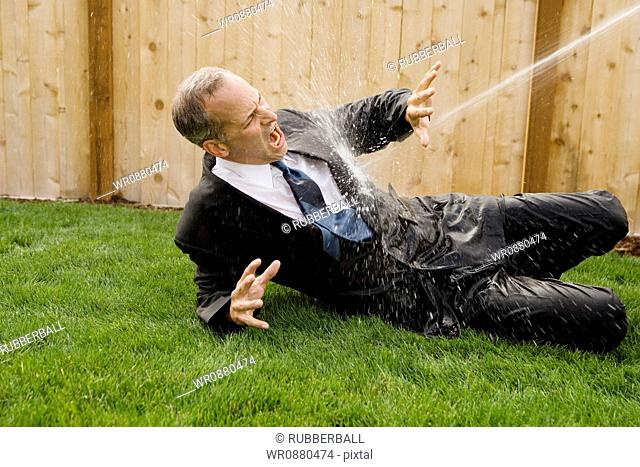 Businessman getting sprayed with water