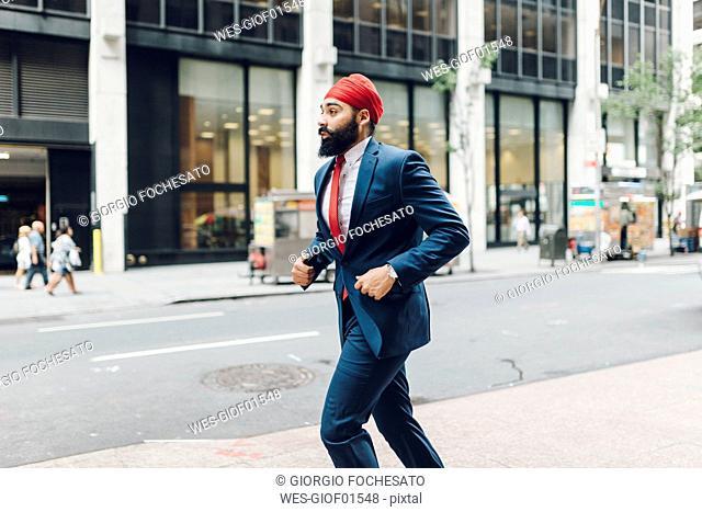 Indian businessman in Manhattan running in the street