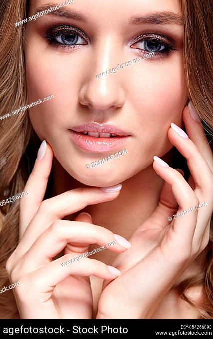 Closeup beauty portrait of young woman. Female with wavy hair. Girl with hands near face